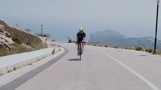 Middle aged strong man fit and healthy climbs a steep and challenging mountain on his professional and expert time trial bicycle isolated and lonely. End of April 2017 in Spain