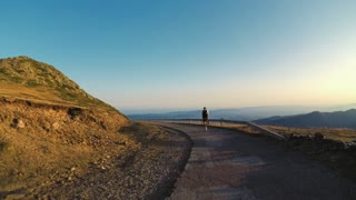Nomad millennial traveler with backpack gear walks explores mountain summit on windy evening with beautiful sunset, his best friend pet dog runs around, both enjoy nature surroundings