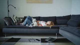 Poor young girl suffers from pain in her belly lying on big sofa at home. Blonde female teenager has strong ache because of her period, spinning on sofa and hopelessly looking advises in internet
