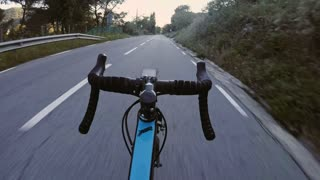 POV of cyclist not holding hands on handlebar and bicycle descending very fast downhill without control. thrilling and dangerous trick performed by athlete on high speed
