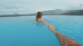 POV of follow me shot of man holding hand of woman girlfriend, walking or swimming in amazing turqouise blue water of natural hot spring or thermal swimming pool, romantic getaway in iceland