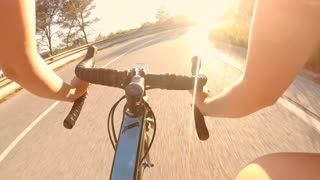 POV of handlebar, cockpit, brakes and gears of a professional road bicycle descending smooth road tarmac on a fast thrilling descent during the training for the race