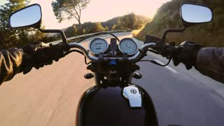 POV of masculine and manly motorcycle driver driving his vehicle through the windy mountain empty road in beautiful scenery on summer day full of thrilling adventures, with light leaks and flares