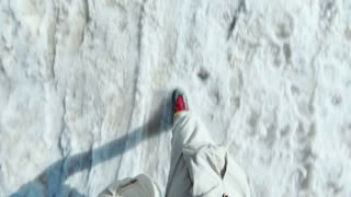 POV shot on action camera of men in cargo pants and blue trekking boots with bright red laces slide down snowy sand slippery slope. Concept fun and adventure, winter and spring sport activity or hobby