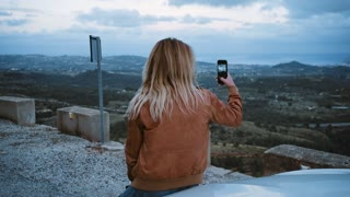 Pretty beautiful blonde selfish woman self centered makes selfie on smartphone while sits on top of car during twilight hours in sunset, beautiful and calm views of independent teenager