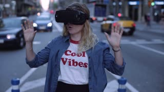 Pretty blonde girl in virtual reality headset on her head is discovering game experience, excitedly touching virtual invisible objects on urban street busy with traffic in twilight