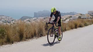 Professional male triathlete doing his hard workout, preparing for next ironman championship challenge, climbs a hill at hot summer day. End of April 2017 in Spain