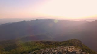 Reverse video drone footage of camera rolling back on cute beautiful couple standing on top of high mountain peak in motivational and inspiring video, romantic goals