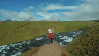 Slowmotion shot of young woman in camping or hiking outfit, red checkered shirt and white tshirt stand next to mountain river and waterfall in iceland, enjoy nature and fresh air, smiles and relax
