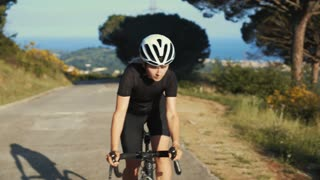 Sporty athletic female rides her professional carbon roadbike on empty mountain road on summer evening in beautiful light, wins race, shows elation and success on top, overtakes competitors