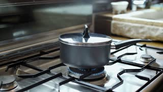 Static shot female petite hand checking on a pan with boiling water, which stands on stainless steel pristine perfectly clean range stove that works on natural gas
