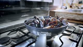 Static shot of deep wok pan on top of vintage steel gas stove full of fresh seafood. Bowl pan with steaming vapor cooked mussels with spices and herbs. Traditional mediterranean cuisine