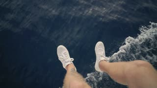 Top view on two sailor legs hanging down overboar of sailing boat that goes forward very fast in deep blue ocean or sea. He wears pure white sneakers and swings his legs above water foam