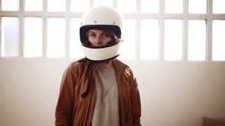 Trendy blonde girl takes off her motorcycle white helmet back at home and laughs and smiles looking into the camera