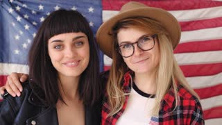 Two patriotic and nationalist conservative women giggle and laugh in the camera, wear hipster outfits red checked shirt,fedora hat, round glasses they wave and stand in front of big american flag