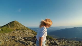 Young beautiful fit lifestyle influencer or blogger, travels around world, inspiring sunset view, hikes or walks on mountain pass summit to enjoy amazing nature, hair blows in wind