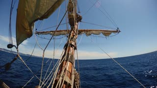 View from nose of old vintage sailing ship waving in deep blue sea with ropes and maintenance thing in air