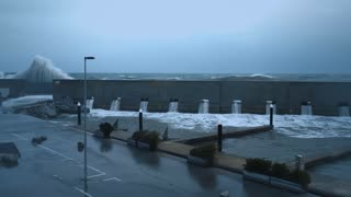 View on strong storm in sea from marina on the shore, huge powerful waves smash coast guard wall