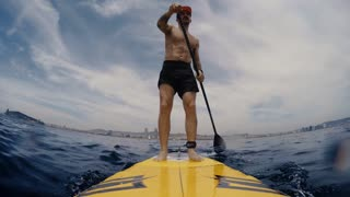 Young Attractive tattooed man on Stand Up Paddle Board, SUP, in the Blue Waters off mediterranean, Active Life Concept