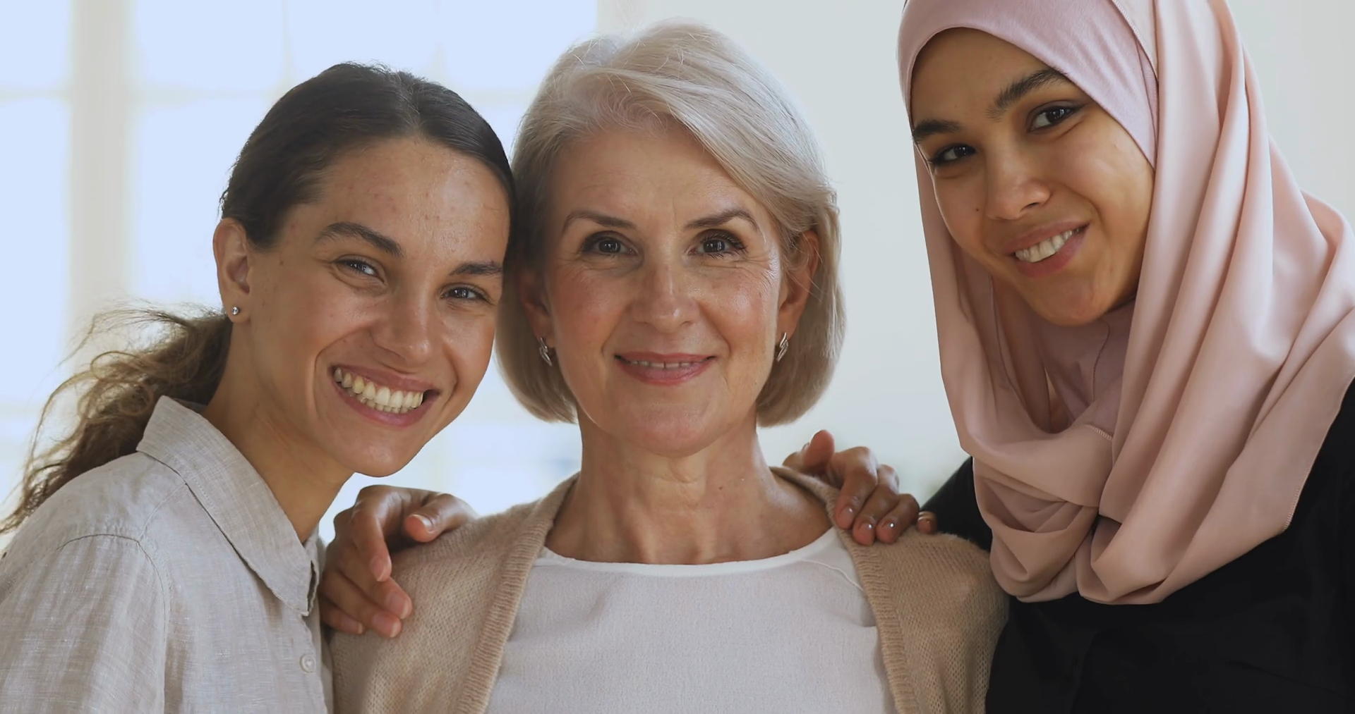 Three diverse smiling women friends embracing looking at