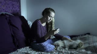 A young sad depressed teenage girl sitting on a bed with her dog in the dark while on her cell phone interacting with Internet social media and text messaging,