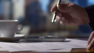 Accountant business person working on tax return forms at desk on calculator