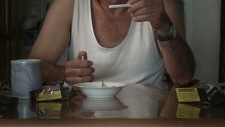 Adult male holding cigarette attempting to quit smoking at table