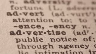 advertise - make publicity for; try to sell (a product); Macro close up of Pencil underlining the word Advertise in fake Dictionary