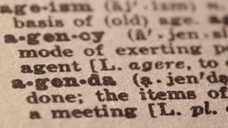 agenda - a temporally organized plan for matters to be attended to. Macro close up of Pencil underlining the word Agenda in fake Dictionary