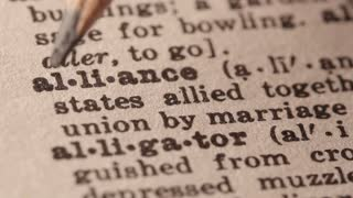 alliance - the state of being allied or confederated. Macro close up of Pencil underlining the word Alliance in fake Dictionary