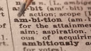 ambition - a strong drive for success  . Macro close up of Pencil underlining the word Ambition in fake Dictionary definition of the word, paper texture visible.