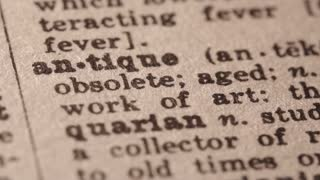 antique - belonging to or lasting from times long ago;. Macro close up of Pencil underlining the word Antique in fake Dictionary definition of the word, paper texture visible.