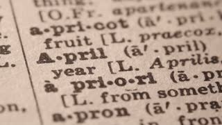 April - the month following March and preceding May. Macro close up of Pencil underlining the word April in fake Dictionary definition of the word, paper texture visible.