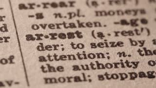 arrest - the act of apprehending (especially apprehending a criminal);. Macro close up of Pencil underlining the word Arrest in fake Dictionary definition of the word, paper texture visible.