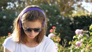 Attractive woman in 20s listening to music with headphones outdoors in park