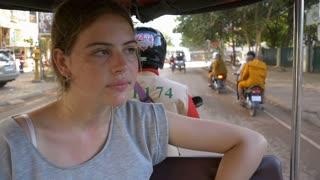 Backpacker tourist girl traveling in asia riding on tuk tuk rural asain villag