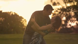 Beautiful Young Couple in Love embrace and kiss outdoors in park