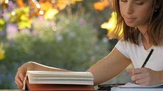 Beautiful young female academic student reading a book studying fall autumn park