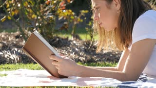 Bookish uni student girl reading a novel book outdoors on college campus