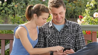 Boy and girl sitting in park listening to music on smart phone device