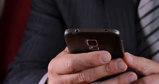Business person in suit texting with mobile smart phone device