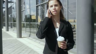 Business woman walking drinking coffee outside building Slow motion