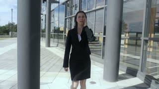 Business woman walking talking on phone outside building Slow motion