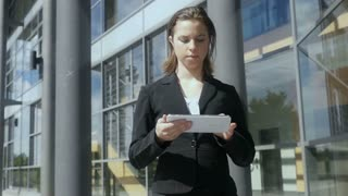 Business woman walking using tablet pc outside building Slow motion