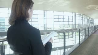 businesswoman walking in office building looking at papers Slow motion