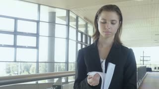 Businesswoman walking looking at papers in office building Slow motion