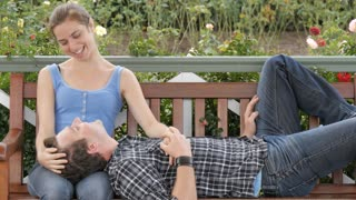 Caring young woman looks lovingly at her partner sitting romantically on bench