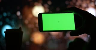 Cell mobile smartphone with Green Screen city night bokeh background