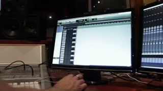 Computer screens in a music recording studio running mixing software