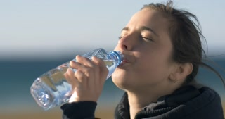 Drinking fresh water from a plastic bottle young adult model woman girl